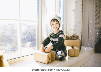 child is sitting by the window on a sunny Christmas day and makes out with gifts in boxes wrapped in paper.dressed in knitted warm woolen clothes and a hat. Inside the house with a stylish interior.