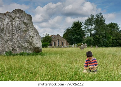 Child sitting in grass near a megalithic standing rock at ancient site of stone circle, a house or chapel in the background, Avebury, England, UK
