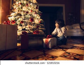 Child sitting near a Christmas tree