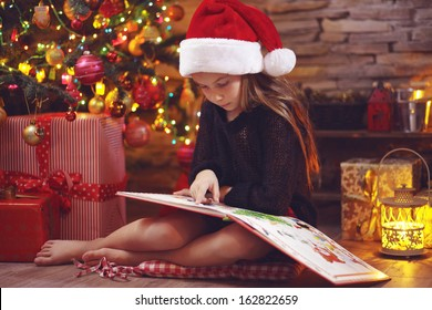 Child sitting near Christmas tree at night at home