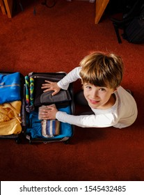 The child sitting on the carpet in the bedroom finishes preparing his suitcase