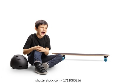 Child sitting on the floor crying and holding knee hurt from a skateboard isolated on white background