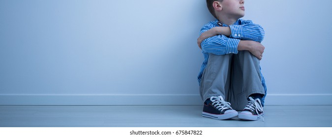Child sitting on the floor in an empty room