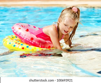Child sitting on inflatable ring in swimming pool.