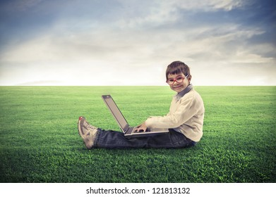 Child, sitting on a lawn, using a laptop computer