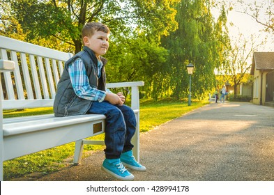 A child sitting on a park bench