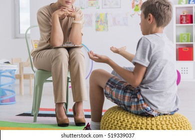 Child sitting on a pouf, talking with a psychologist