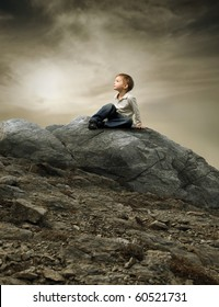 Child sitting on a rock