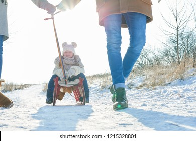 Child sitting on sled and driving on snow with happy family