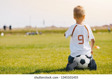 Child sitting on soccer ball on the football pitch. Kid in sports jersey uniform watching soccer training on a sunny summer day