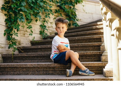 Child sitting on the stone steps. Portrait of handsome kid boy wearing casual sitting on the stairs on the street. Stylish boy looking at camera.