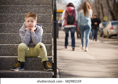 Child sitting on the stone steps. Portrait of handsome kid boy wearing casual sitting on the stairs on the street. Stylish boy looking at camera. Teenage boy, child outdoors in summer or spring.