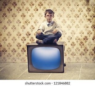 Child sitting on a television