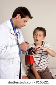 Child sitting on a treatment bed as a doctor or paediatrician takes his blood pressure.