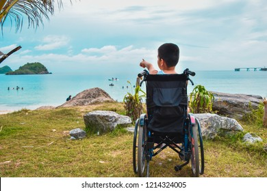A child sitting on a wheelchair by the sea. He pointed his hand forward with excitement. He is a physically handicapped child. But he is happy like other children.