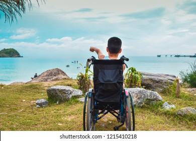 A child sitting on a wheelchair by the sea. He pointed his hand forward with excitement.
