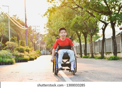 Child sitting on wheelchair is enjoying activities in the park like other people. Happy disabled kid concept.