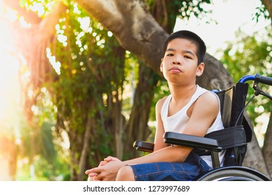 Child sitting on a wheelchair. He came to rest in the park but was not happy.