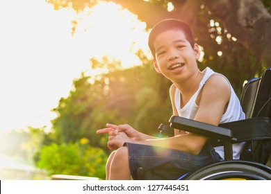 Child sitting on the wheelchair. He spent time in the park to restore the body and strengthen his mind. Orange light shines in his face. Happy disabled kid concept.