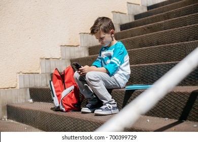 Child sitting outside school and playing games on his cell phone. Schoolboy taking a break from school and browsing his mobile.