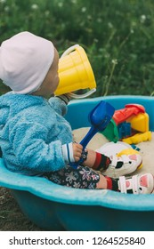 the child is sitting in the sandbox and playing in the sandbox toy balls,shovel, rakes and buckets