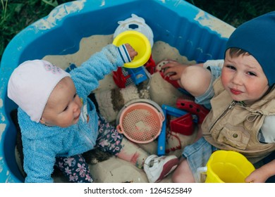 the child is sitting in the sandbox and playing in the sandbox toy balls, shovel, rakes and buckets