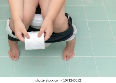 Child sitting in toilet and holding tissue roll, diarrhea constipation. health and cleanliness concept