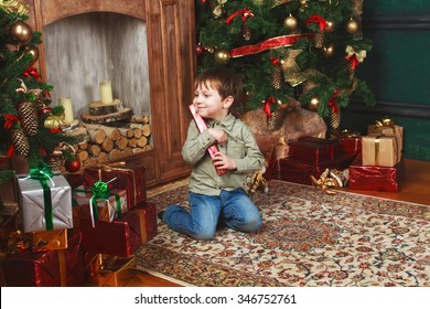 child sitting under the Christmas tree with gifts