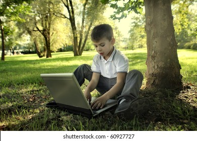 Child sitting under a tree in a garden and using a laptop