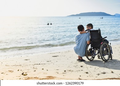 A child sitting in a wheelchair hugging his father's neck at the seaside.