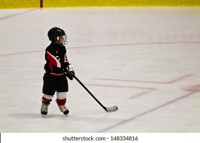 Child skating and playing hockey in an arena