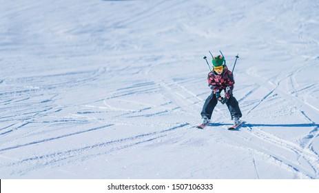 Kinderski in den Bergen. Aktives Jugendkind mit Schutzhelm, Schutzbrille und Skistöcken, die die Skipiste hinunter laufen.  Schneelandschaft, sonniger Tag in der Wintersaison