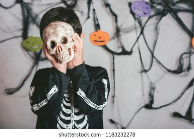 child with a skull covering his face at halloween party