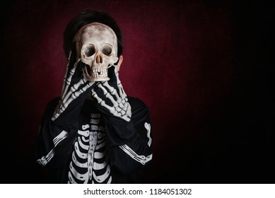 child with a skull covering his face on halloween