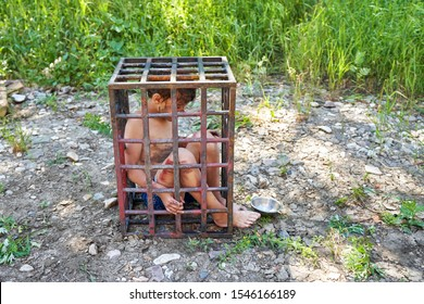 Child slavery. A dirty child is sitting in an iron cage outside, an empty bowl is next to him