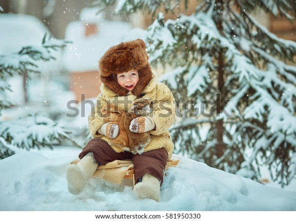 Child sledding. Toddler kid riding a sledge. Children play outdoors in snow. Kids sled in winter.  Little rabbits in the hands.