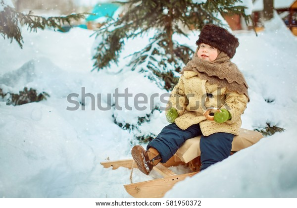Child sledding. Toddler kid riding a sledge. Children play outdoors in snow. Kids sled in winter.
