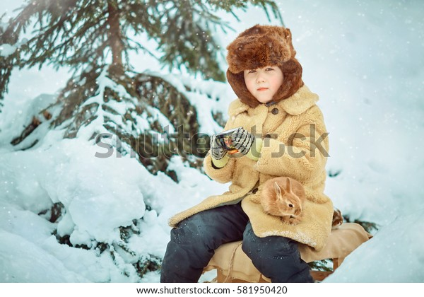 Child sledding. Toddler kid riding a sledge. Children play outdoors in snow. Kids sled in winter.  Cup with pattern in hand. Drinking tea in the cold. Warming after the game