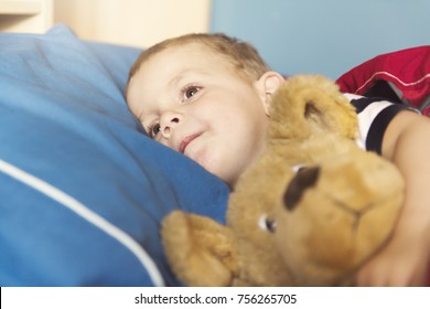 A Child sleeping in his bed with teddy