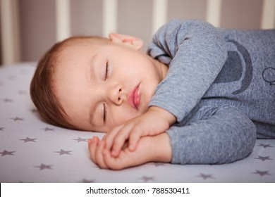 the child sleeps in the gray pajamas on the baby bed