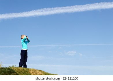 child (small boy) looking in the sky with a trace of the plane