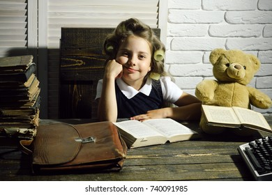 child or small girl with curler in hair read book with briefcase and retro typewriter on table in secretary or business cabinet