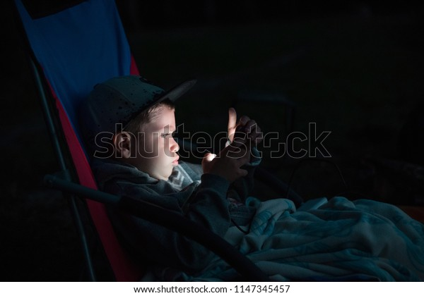 child smartphone playing games and watching cartoons at night on the street, child addiction