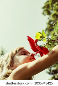 child smelling a blooming flower