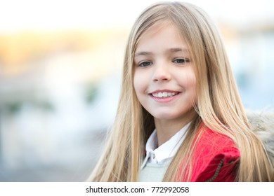 Child smile on blurred environment. Girl with blond long hair on autumn day outdoor. Happy childhood concept. Kid fashion and style. Beauty, look, hairstyle.