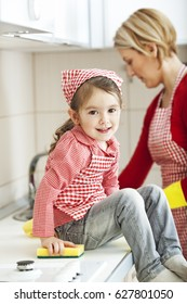 Child smiling in front of her mother cleaning the kitchen