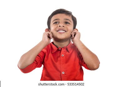 A child smiling and pulling his ears