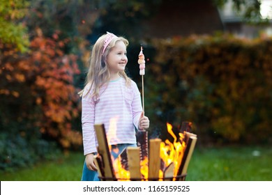 Child with smores at camp fire. Kids roast marshmallow on stick at bonfire. Autumn family outdoor fun. Camping with children in fall forest. Little girl roasting marshmallows.