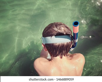 child with snorkeling mask from the back about to dive into the sea on a sunny day