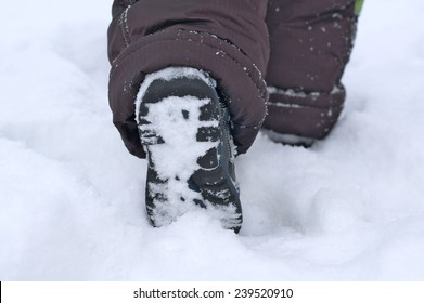 Child snow boot footprint footing and stepping in winter, footstep hiking trail, walking away shoes feet step by step, winter sports activity concept